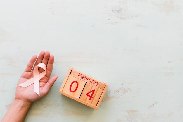 Main tenant le ruban de conscience rose et boîte en bois du 4 février sur toile de fond Photo gratuit