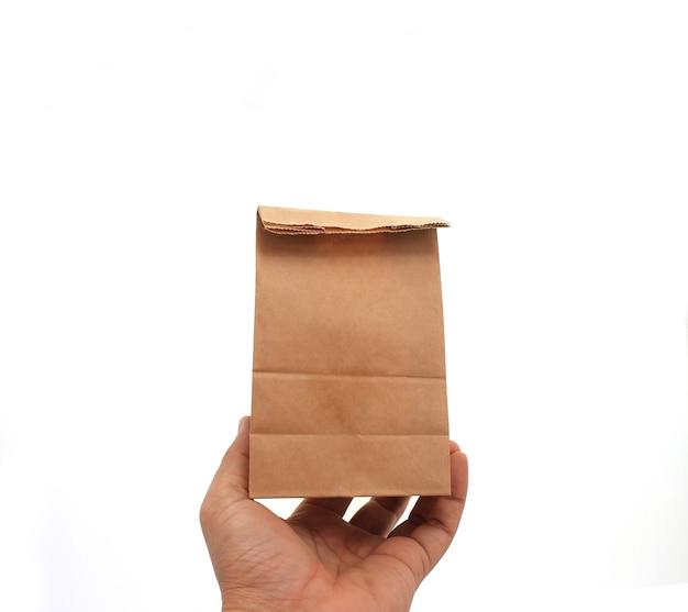 Main tenant un sac en papier brun Photo Premium
