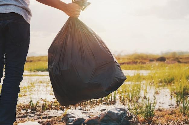 Main tenant un sac poubelle noir à la rivière pour le nettoyage avec le coucher du soleil Photo Premium