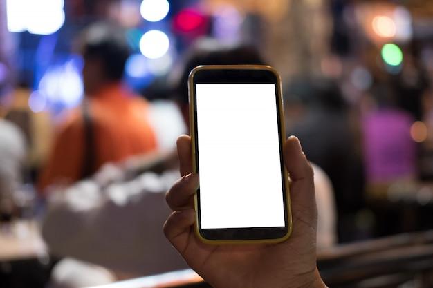 Main tenant le smartphone dans un pub. Photo Premium