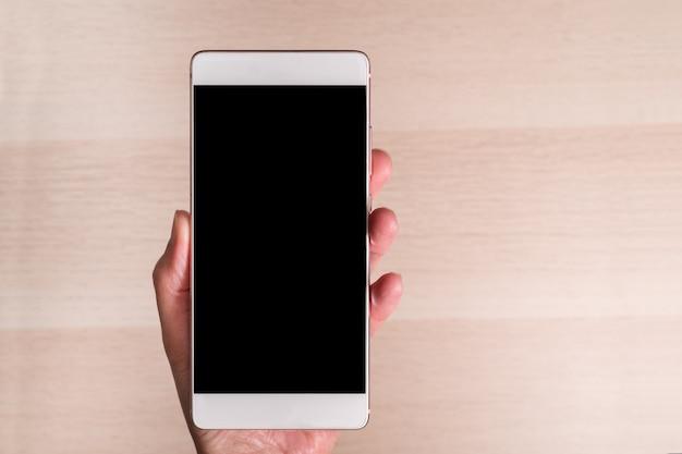 Main tenant le smartphone avec écran blanc isolé sur fond en bois Photo Premium