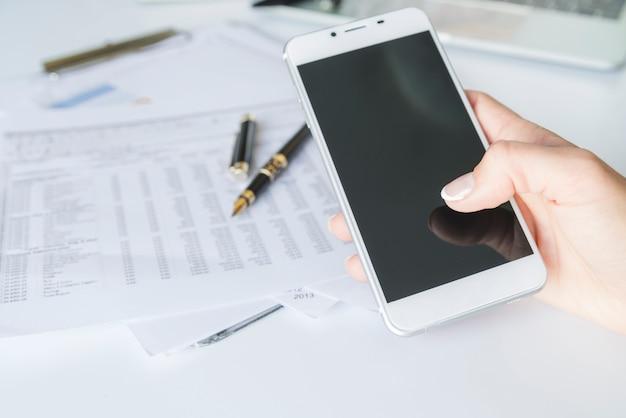 Main tenant un smartphone sur le lieu de travail Photo gratuit