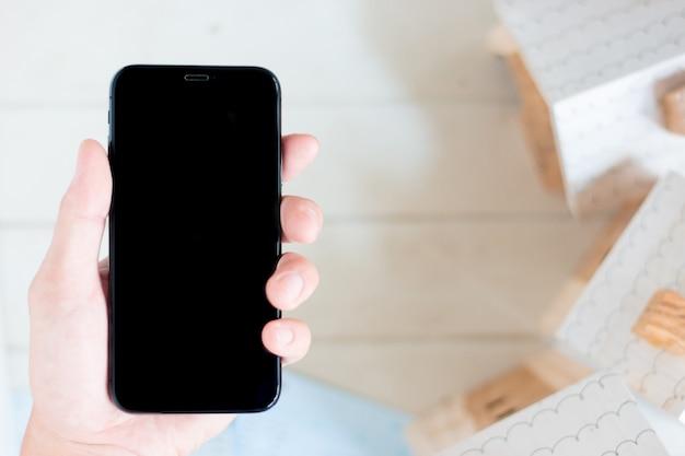 Main tenant un smartphone avec livre de comptes et modèle de maison miniature Photo Premium