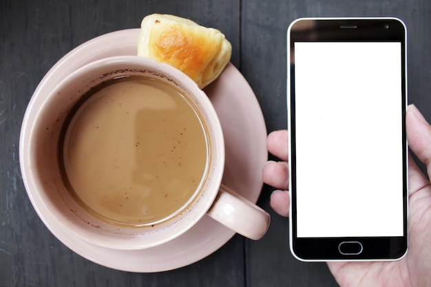 Main tenant le smartphone avec une tasse de café brune sur une table en bois noire Photo Premium
