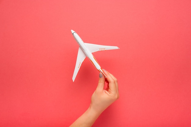 Main Tenant Soigneusement Le Modèle. Avion Sur Fond De Couleur Rose. Photo Premium