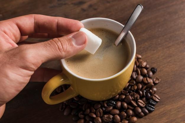 Main tenant le sucre près de la tasse à café Photo gratuit
