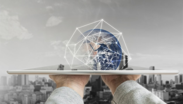 Main tenant une tablette numérique avec la technologie de connexion réseau globale et des bâtiments modernes Photo Premium