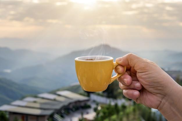 Main Tenant Une Tasse Blanche De Tasses à Café Expresso Chaud Et Vue Sur La Nature Du Paysage De Montagne Le Matin Avec La Lumière Du Soleil Photo Premium