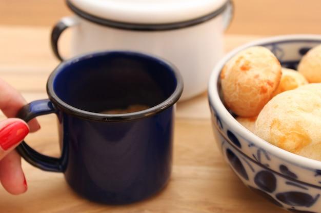 Main tenant une tasse de café et de bol à pain au fromage brésilien (pão de queijo) sur la table. Photo Premium