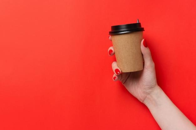 Main tenant la tasse de café en papier sur fond rouge. Photo Premium