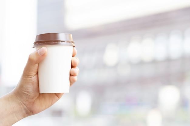 Main tenant une tasse de papier à emporter boire du café à la lumière naturelle du soleil du matin. Photo Premium