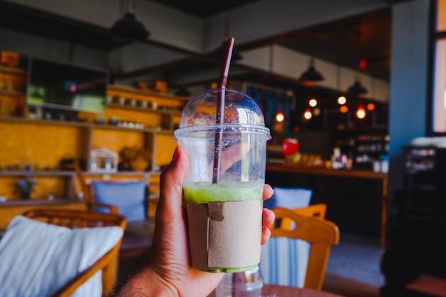Main tenant une tasse en plastique de thé vert dans un environnement de café Photo Premium