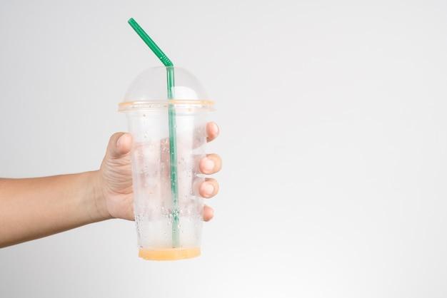 Main Tenant Une Tasse En Plastique Vide De Thé Glacé Au Lait Thaïlandais Avec Paille Verte Photo Premium