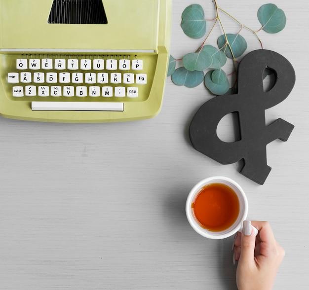 Une main tenant une tasse de thé avec une machine à écrire rétro Photo Premium