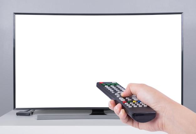 Main tenant la télécommande du téléviseur avec tv led et écran blanc Photo Premium
