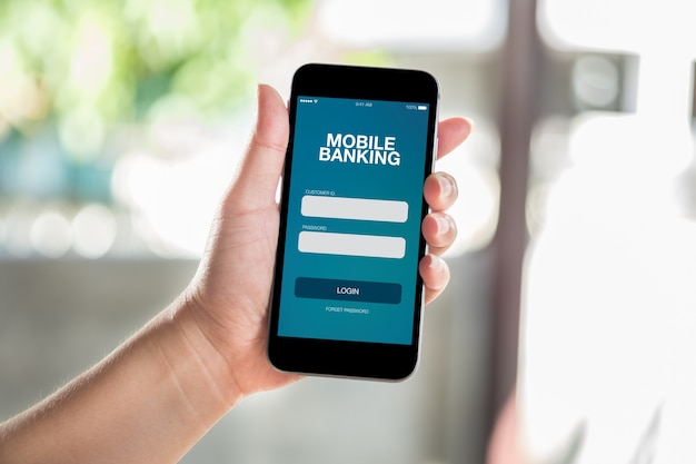 Main tenant un téléphone intelligent mobile avec écran de services bancaires mobiles Photo Premium