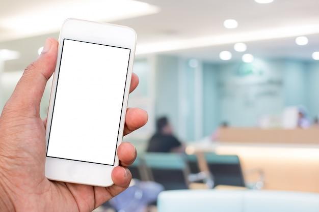 Main tenant un téléphone mobile intelligent avec écran blanc en position verticale Photo Premium