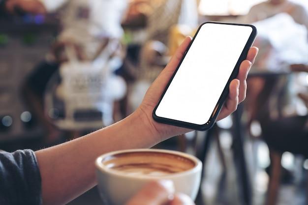 Une Main Tenant Un Téléphone Mobile Noir Avec écran Blanc Tout En Buvant Du Café Dans Un Café Vintage Photo Premium