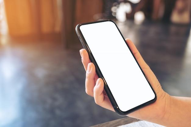 Une Main Tenant Un Téléphone Mobile Noir Avec écran De Bureau Blanc Vierge Photo Premium