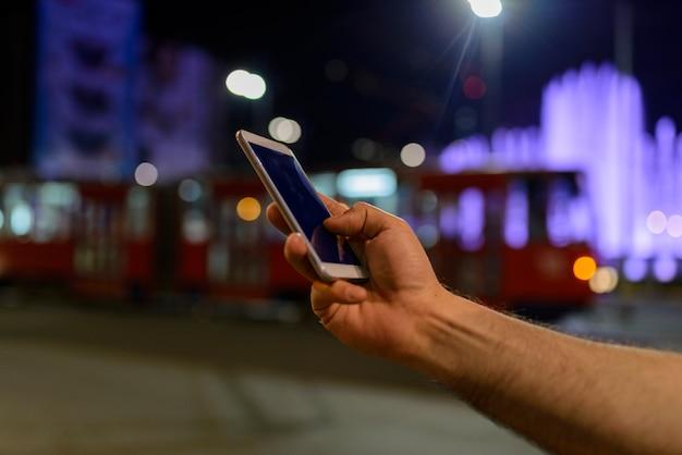 Main tenant un téléphone noir coupure à l'intérieur avec bokeh Photo Premium