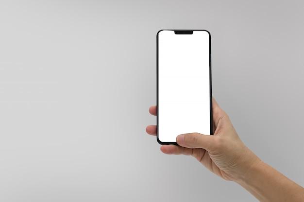 Main tenant un téléphone portable noir avec écran blanc isolé sur fond gris Photo Premium