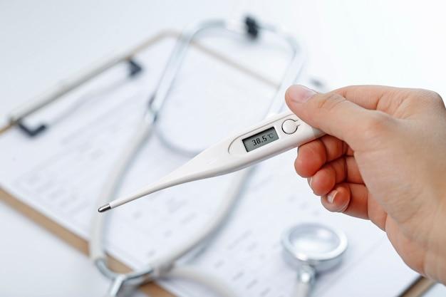 Main tenant une température corporelle de mesure du thermomètre Photo gratuit