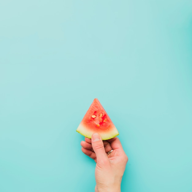 Main tenant une tranche de melon d'eau Photo gratuit