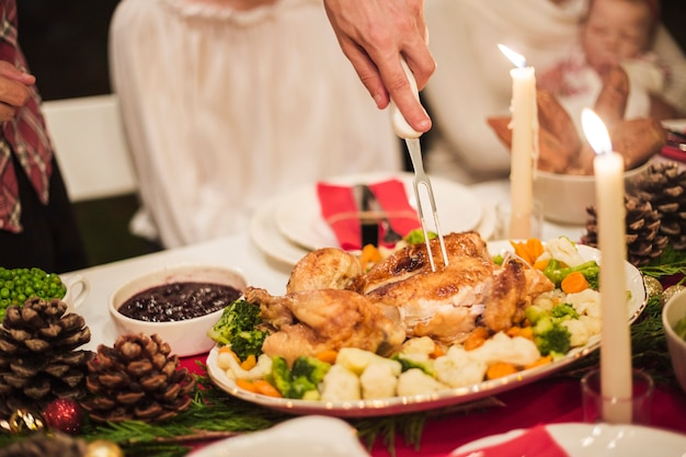 Main tenant la turquie avec une fourchette à la table de noël Photo gratuit