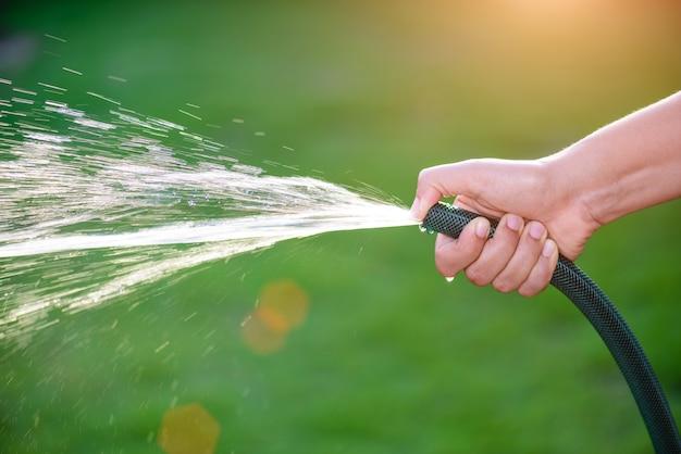 Main tenant le tuyau d'eau et utilisant un doigt proche pour faire de l'eau pulvérisée avec la lumière du soleil Photo Premium