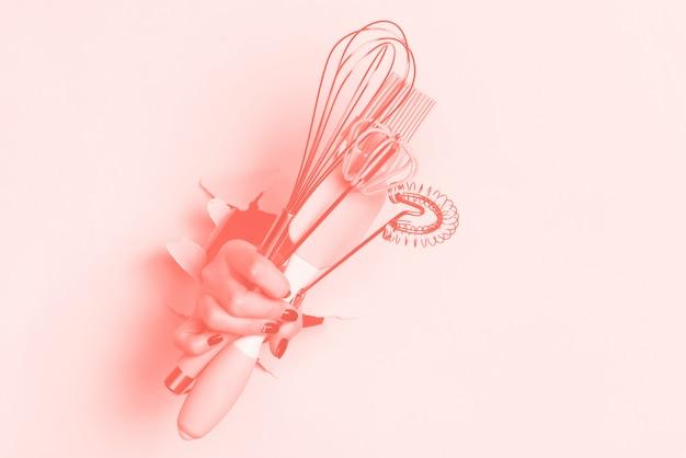 Main tenant des ustensiles de cuisine. outils de cuisson - pinceau, fouet, spatule. boulangerie, cuisine, concept de cuisine maison saine Photo Premium