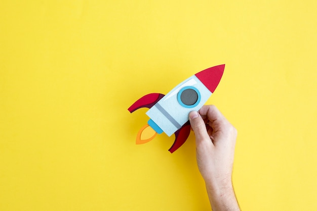 Main tenant le vaisseau spatial de fusée sur fond jaune Photo Premium