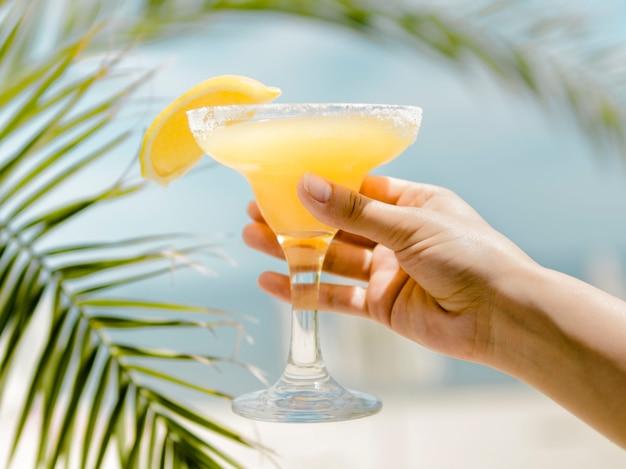 Main tenant un verre à cocktail froid orange avec une boisson rafraîchissante Photo gratuit