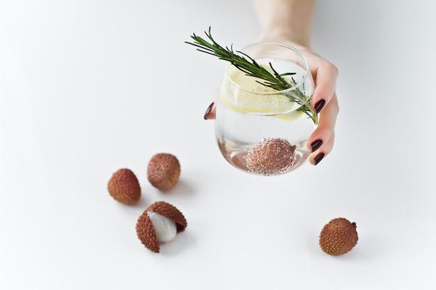 Main tenant un verre d'eau claire avec citron, romarin, litchi. Photo Premium
