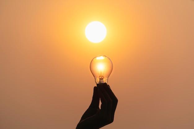 Main tenir une ampoule sur fond de coucher de soleil pour économiser de l'énergie Photo Premium