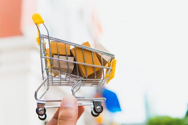 Main tenir la boîte de papier dans le mini panier en utilisant comme concept de commerce électronique, les achats en ligne et les entreprises Photo Premium