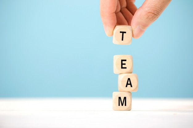 Main Tenir Les éléments De Cube En Bois Avec La Lettre Sur La Table En Bois, Qui Représente L'équipe. Concept D'affaires Photo Premium
