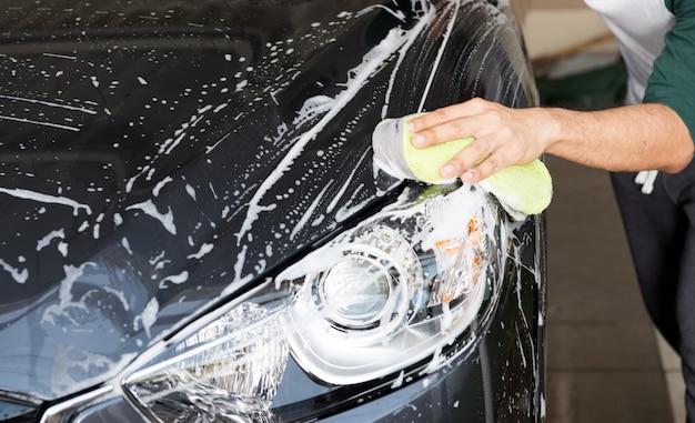 Main tenir l'éponge sur la voiture pour la laver Photo Premium