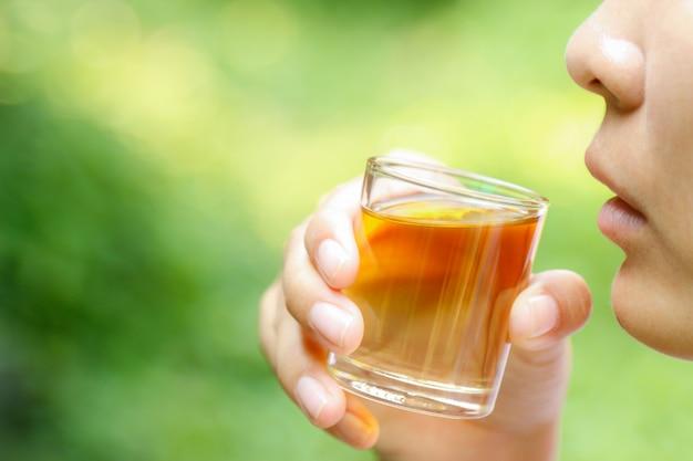 Main tenir l'huile de fines herbes pour une consommation saine Photo Premium