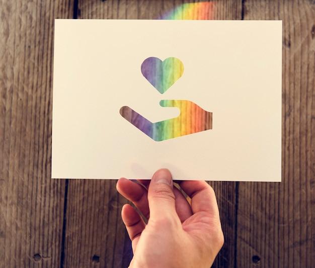 Main tenir main et coeur papier sculpture avec lumière de prisme Photo gratuit