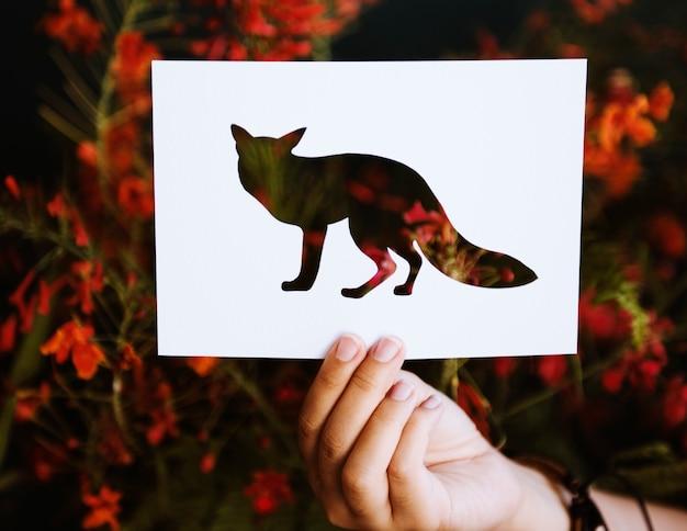 Main tenir le papier de fox sculpture avec le fond de la nature Photo gratuit
