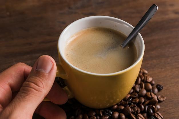 Main, tenue, tasse, à, cuillère, et, café Photo gratuit