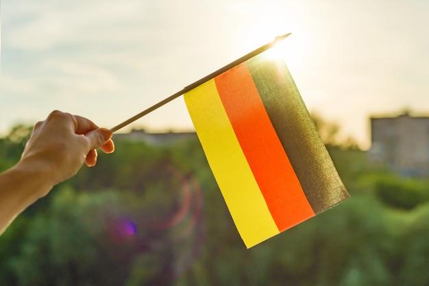 Main tient le drapeau de l'allemagne une fenêtre ouverte Photo Premium