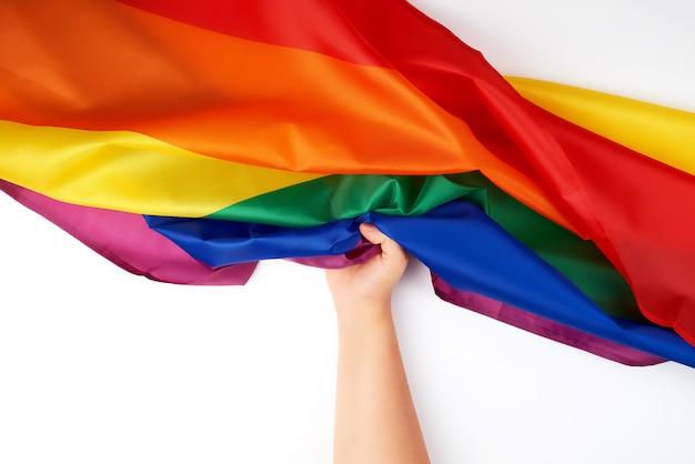Main tient le drapeau arc-en-ciel en textile, symbole de la liberté Photo Premium