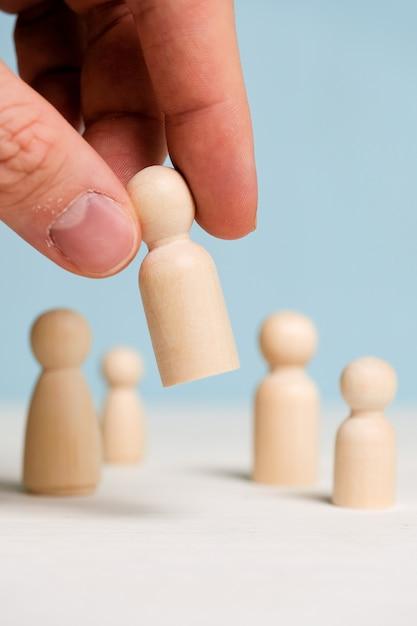 Une main tient une figurine en bois sur un fond bleu. concept de construction d'équipe. fermer. Photo Premium