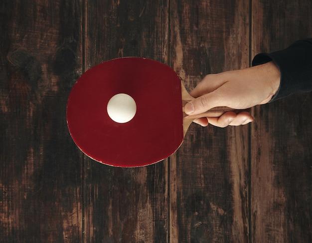 Main Tient Une Fusée Professionnelle Au-dessus De La Table En Bois Vieilli Avec Ballon Dessus Et Prêt à Jouer Au Ping-pong Photo gratuit