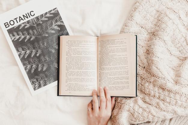 Main Touchant Le Livre Sur L'affiche Et La Couverture Sur Le Drap De Lit Photo gratuit