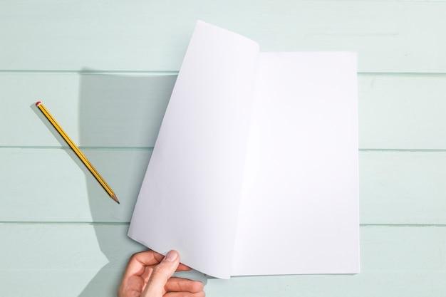 Main tourner une page blanche à plat Photo gratuit
