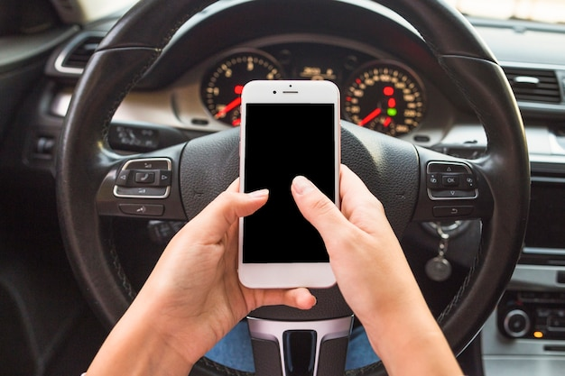 Main en utilisant le téléphone portable devant le volant dans la voiture Photo gratuit