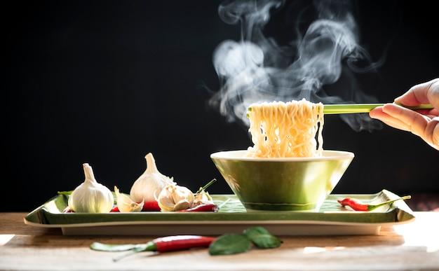 Main utilise des baguettes vertes pour ramasser les nouilles. concept de la malbouffe Photo Premium