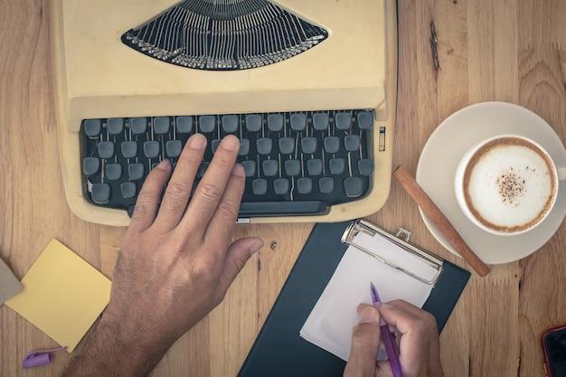 Main utilise des machines à écrire vintage sur une table en bois. Photo Premium